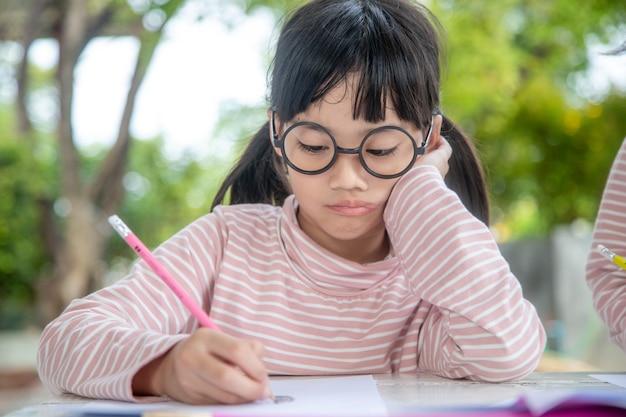 教室で本を書く小さなアジアの女の子