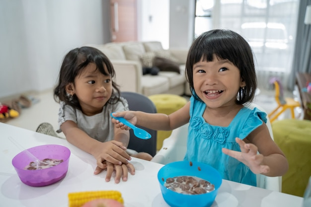 一緒に朝食を持つ小さなアジアの女の子