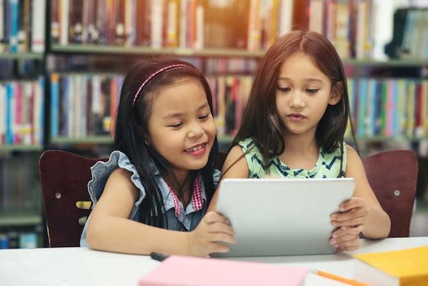 デジタルタブレットデバイスで遊んでいる小さなアジアの女の子。 2人の美しい妹がテーブルに座って、図書館のタブレットpcで遊んでいます。