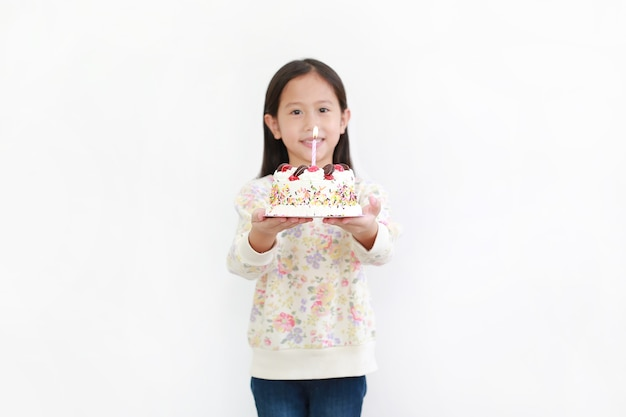 Little asian kid girl giving happy birthday cake for you on white background. focus at cake.