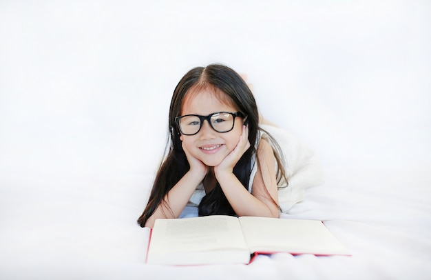 Little asian kid girl wearing glasses reading hardcover book lying on bed against white background.