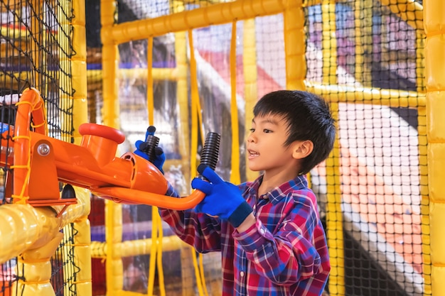 Little asian kid is having fun playing with ball cannon in indoor playground