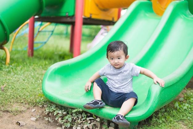 小さなアジア人の子供が遊び場で滑る