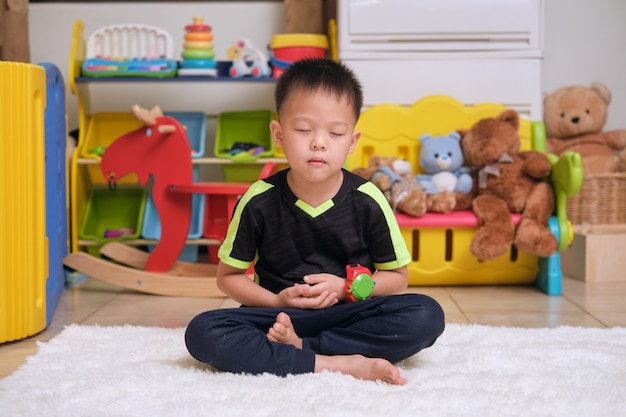 Little asian kid with eyes closed barefoot practices yoga meditating to relieve negative emotions