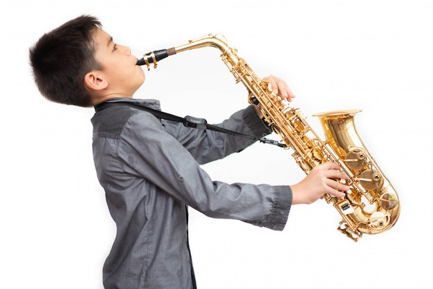 Little asian musician boy playing saxophone