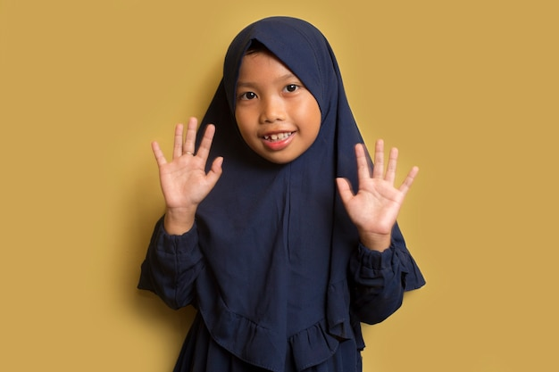 Little asian muslim girl waving hands, welcoming and greeting you