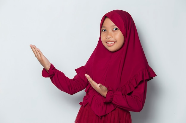 Little asian muslim hijab girl pointing with fingers to different directions