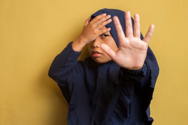 Little asian muslim hijab girl show stop hands gesture