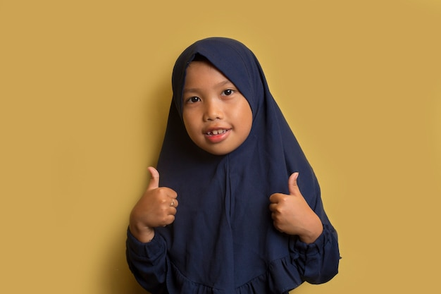 Little asian muslim hijab girl show thumbs up gesture