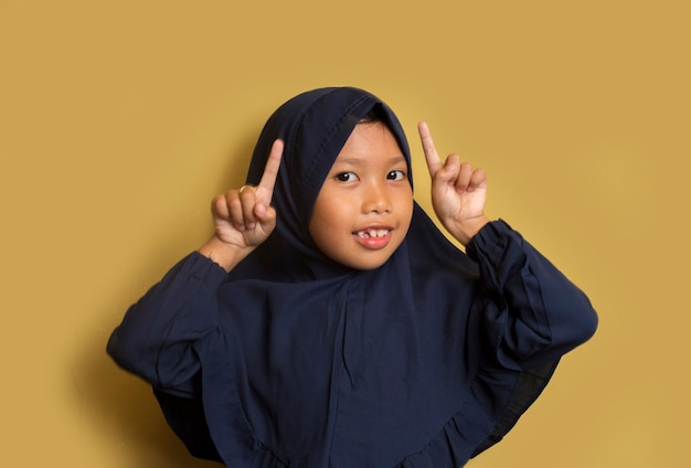 Little asian muslim hijab girl with hand point on empty space
