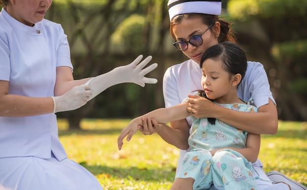 タイのバンコクの病院の緑豊かな公園で医者から健康診断を受けるために女性看護師と一緒に座っている小さなアジアの患者の女児。