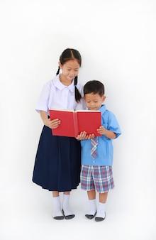 작은 아시아 학교 소년과 소녀 흰색 배경에 고립 된 책을 읽고와 태국 학교 유니폼 서. 전체 길이