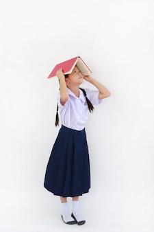 태국 교복을 입은 작은 아시아 여학생이 흰색 배경에 격리된 머리 위로 열린 책 표지를 들고 서 있습니다. 전체 길이