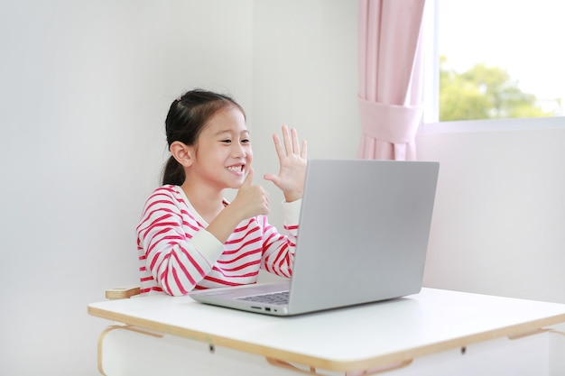 Little asian schoolgirl study online learning class by video call on laptop