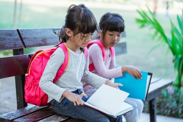 공원에 함께 앉아 있는 작은 아시아 학생