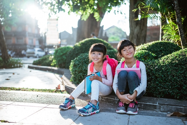 Little asian student sitting in the park together