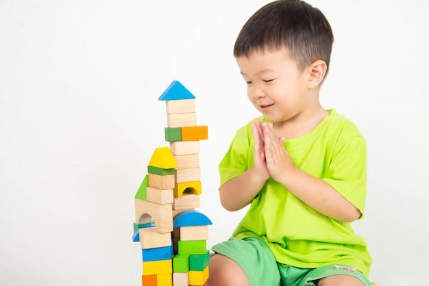 Little asian toddler boy playing wood blocks wear helmet engineer