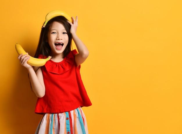 Маленькая азиатская женщина в красной блузке, красочной юбке. выглядел удивленно, держа один банан в руке, другой лежал на голове, беззубый рот, позируя на оранжевом фоне. фрукты, эмоции