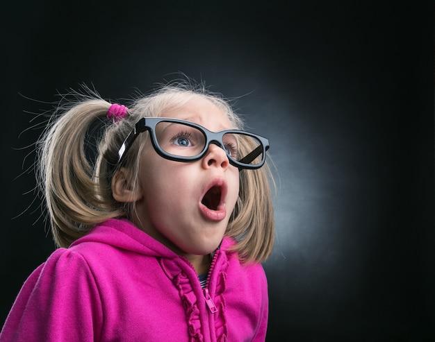 面白い大きな眼鏡をかけた小さな驚いた女の子
