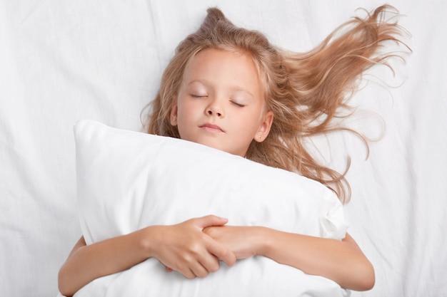 Маленькая привлекательная дочь с закрытыми глазами, обнимает мягкую белую подушку во время сна