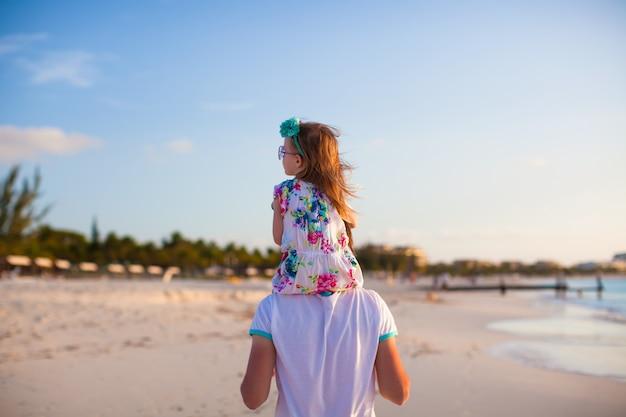 Little ã'âãâ³ãâµã'⃠girl riding on her dad walking by the beach