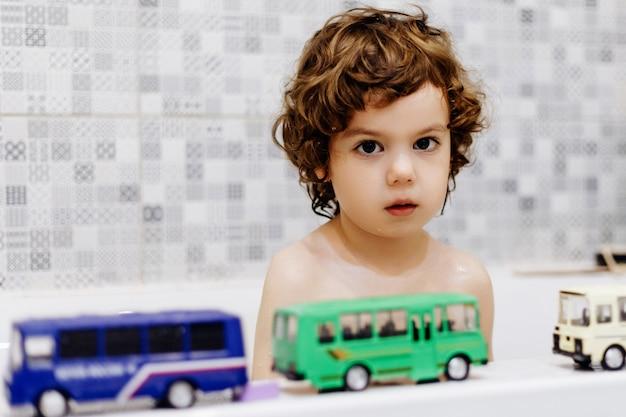 Маленький аутичный мальчик в ванной комнате играет с игрушечным автобусом