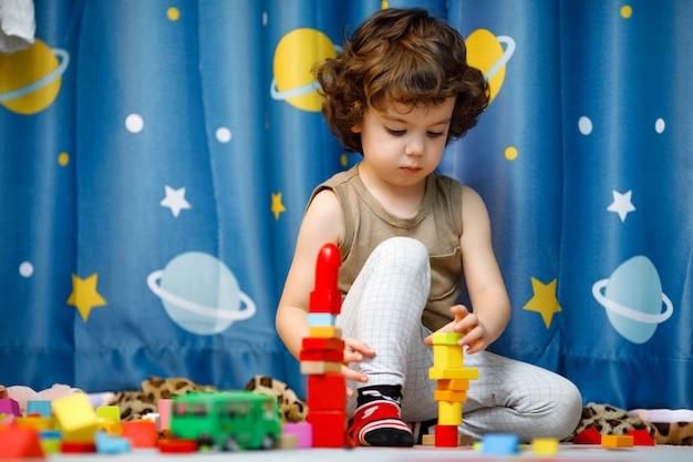 Маленький аутичный мальчик играет с кубиками дома