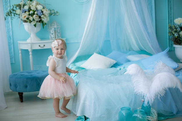 Little baby 1 year from birth sitting on a bed or on a chair in a pale blue children's room.