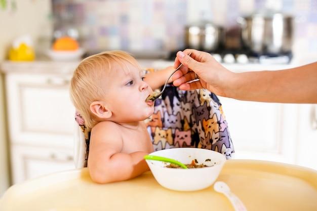 Маленький ребенок дома сидит за столом и ест.