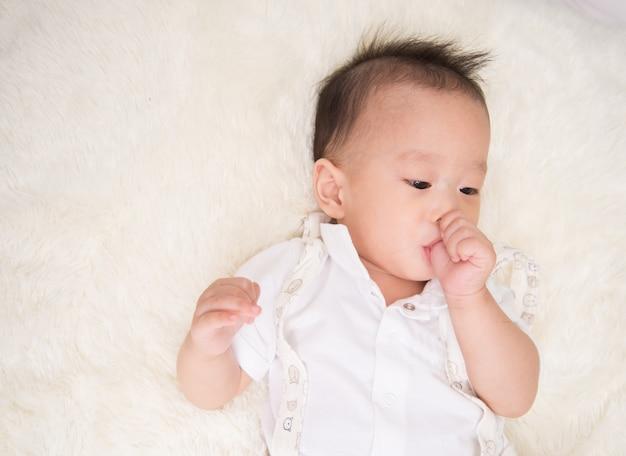 口の中に親指で7ヶ月の小さな男の子