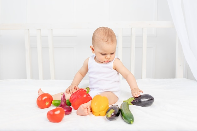 Little baby boy 8 months old sitting on the bed in the nursery with vegetables, baby feeding, baby food concept