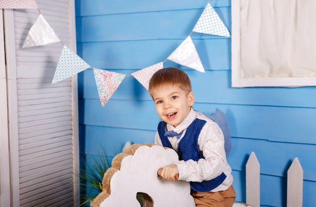 Little baby boy celebrating his birthday. birthday party for cute child. surprised kid looking at camera on blue wall. fun, joy, celebration and holiday. trendy children clothes, party concept