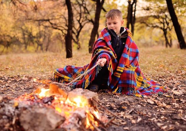 Маленький мальчик, покрытый красочным пледом, сидит у костра на фоне осеннего леса.