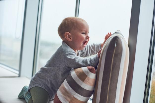 Маленький мальчик crawlibg возле большого окна на подушках.