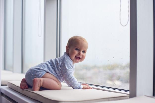 Маленький мальчик ползет возле большого окна