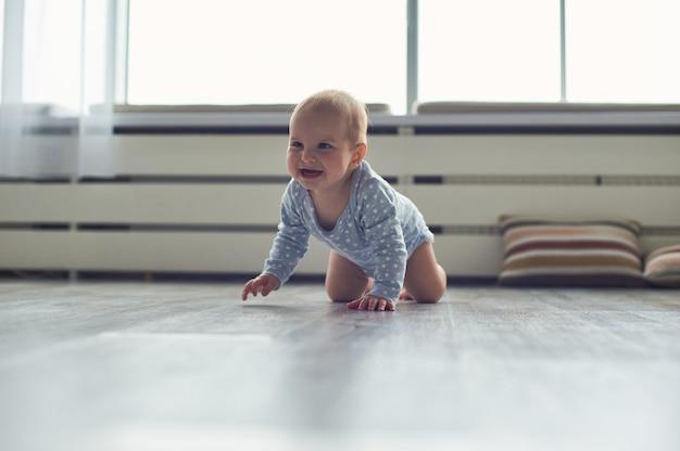 Маленький мальчик ползет по полу дома