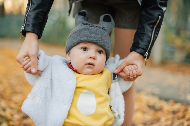Little baby boy holding mom hands in autumn