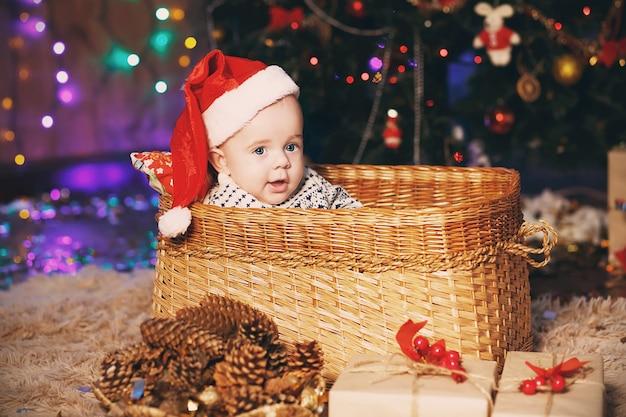 籐のかごに座っているサンタの帽子の小さな男の子。新年とクリスマスのコンセプト