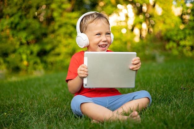 笑顔の夏の公園で屋外でタブレットコンピューターを保持しているワイヤレスヘッドフォンで小さな男の子