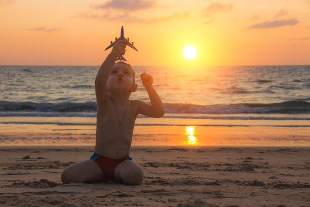 小さな男の子は、日没時にタイのアンダマン海の素晴らしい熱帯のビーチの砂の上でおもちゃの飛行機で遊んでいます。子供と飛行機で旅行の概念。家族の休日。