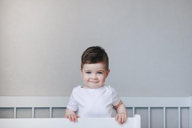 어린 소년은 하얀 침대에서 웃고 아름다운 눈을 가진 행복한 어린 시절 개념 유아
