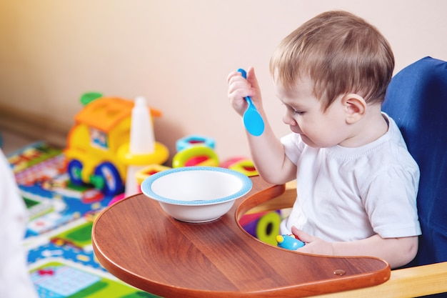 Little baby boy learning to eat at a table studying a plate and spoon in the kitchen