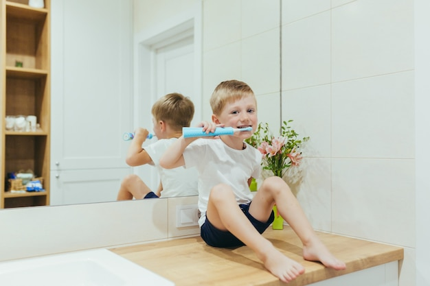 Little baby boy learns to brush his teeth in the bathroom