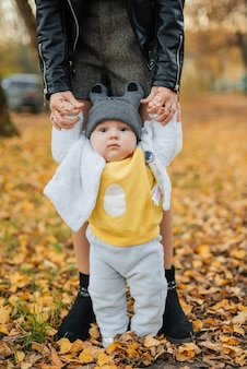 Little baby boy learns to take first steps holding mom hands in autumn