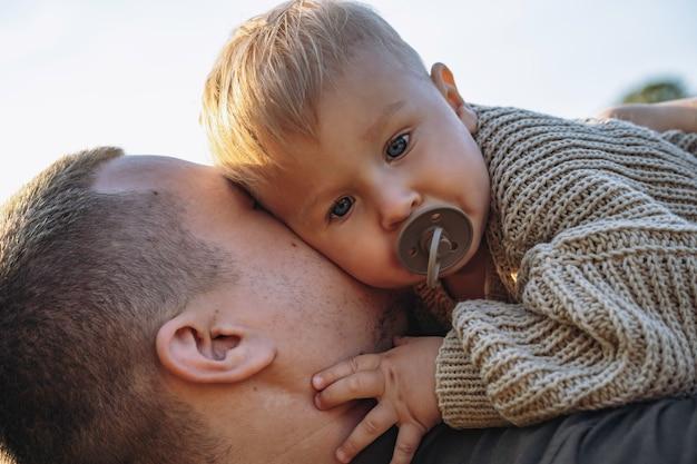 젖꼭지를 빠는 그의 아빠의 손에 작은 아기. 야외에서 함께 시간을 보냅니다. 아버지의 날. 고품질 사진