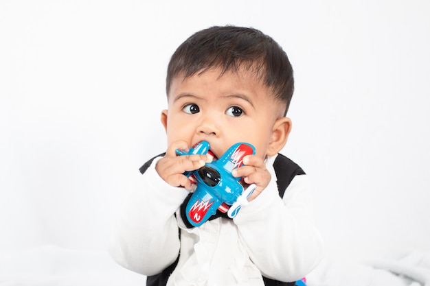 Little baby boy play and bite toy