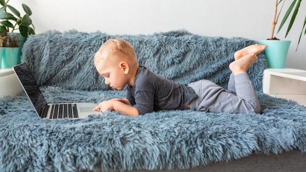 집에서 소파에 누워 노트북에 작은 아기 소년. e- 학습, 거리 공부, 거리 통신 개념