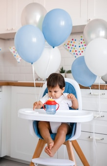 Little baby boy sitting in blue high chair at home on white kitchen and drinking water from sippy cup on background with balloons.