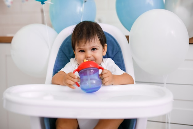 Little baby boy sitting in high chair at home on white kitchen and drinking water from sippy cup on background with balloons.