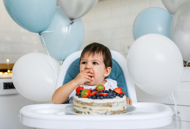 Little baby boy sitting in high chair in white kitchen and tasting first year cake with fruits on background with balloons.